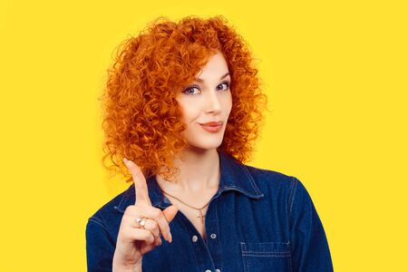 woman gesturing a no sign. Closeup portrait unhappy, serious redhead curly hair girl raising finger up saying oh no you did not do that yellow background. Negative emotions facial expressions feelings 免版税图像