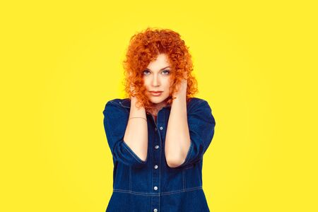 Hear no evil concept. Portrait of young attractive redhead woman curly hair retro style covering with hands her ears eyes opened isolated on yellow wall background Stock Photo