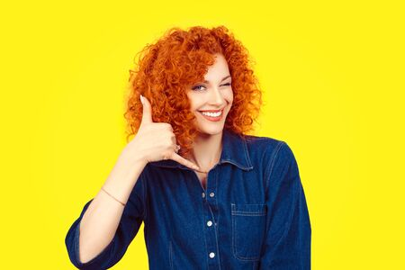 Give me a call. Closeup portrait young red head curly single woman excited happy student winking with eye making showing call me gesture sign with hand shaped like phone isolated yellow background.