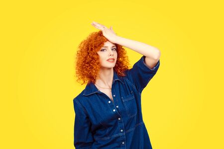 Regrets wrong doing. Closeup portrait silly young redhead curly woman slapping hand on head having duh moment isolated yellow background Negative human emotion facial expression body language reaction