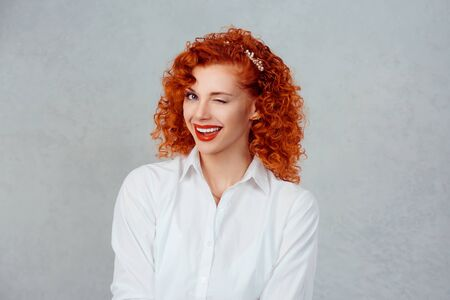 Successful business woman. Closeup portrait head shot pretty confident redhead curly girl winking isolated gray background wall. Positive human emotion face expression feeling life perception