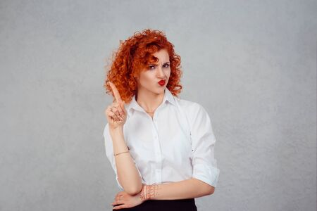 woman gesturing a no sign. portrait unhappy, serious redhead curly retro style girl raising finger up saying oh no you did not do that gray grey background. Negative emotions facial expression feeling 版權商用圖片