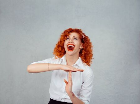 Too many things to do. Young redhead curly woman showing time out hand gesture, frustrated screaming to stop isolated on gray grey wall background. Human emotions face expression feelings reaction