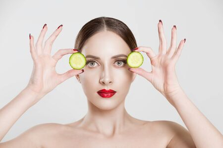 Young serious beautiful woman holding cucumber slices on the face looking at you camera isolated white grey background wall