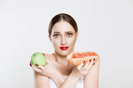 Portrait of beautiful young woman holding tasty hot-dog and green apple in crossed hands, looking at camera, having doubts what to choose, isolated on white background. Face expression, body language. Stockfoto