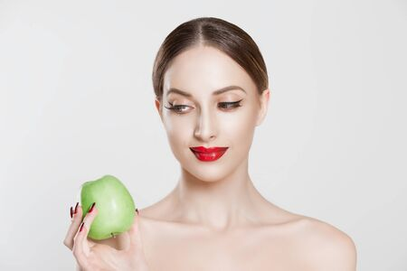 Diet is good. Beautiful woman holding looking at green apple isolated white background
