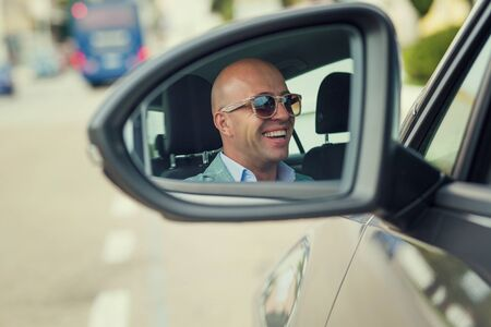 Closeup portrait of side view mirror car reflection of handsome business man driver driving car looking to the road, isolated outdoors background. Banque d'images