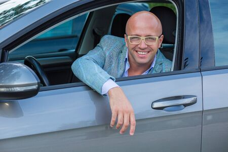Handsome man smiling in his new car
