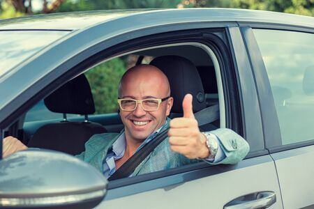 Business man in his car smiling, showing thumbs up