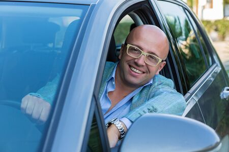 Handsome business man smiling looking out of his new car window