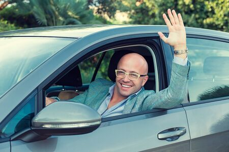 Handsome young business man raised hand out of the window of the car. Italy country car trip Stock fotó