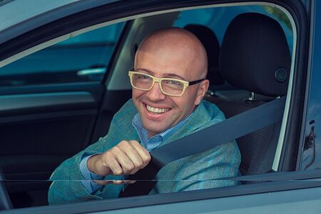 Handsome man smiling looking at camera in his car asking showing you to fasten safety belt. Safe trip transportation and vehicle concept.