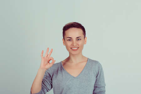 Beautiful young woman showing Ok sign isolated on green white wall background. Positive human emotions face expression body language. Horizontal studio shot 免版税图像 - 151027862