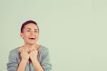 Win. Closeup portrait happy ecstatic winning successful young woman fist hand in the air celebrating being winner isolated green background. Positive human emotions body language. Achievement concept