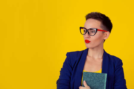 beautiful business woman short hair style girl with a book isolated yellow background copy space. Blue formal suit shirt.  Daydreaming thinking head in clouds concept. Student planning dream