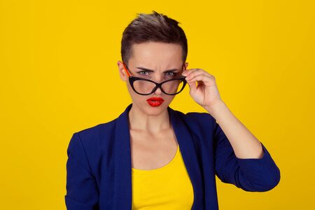 Closeup portrait beautiful young business woman lady looking at you camera over glasses gesture skeptically isolated yellow background. Negative human emotions, facial expression feeling body language