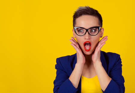 Wow. Close up portrait young business woman beautiful girl short hair looking excited holding her mouth opened, hands on cheeks, isolated yellow wall. Shocked surprised stunned. Positive human emotion