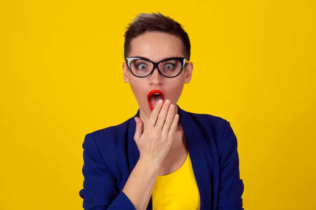 Surprised woman. Wow. Close up portrait young woman beautiful girl short brown hair looking excited  mouth opened hands on mouth isolated yellow wall. Shocked surprised stunned. Positive human emotion Reklamní fotografie