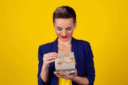 Happy excited beautiful business woman short hair style girl looking to received gift isolated yellow background copy space. Blue formal suit shirt red lips daily make up.