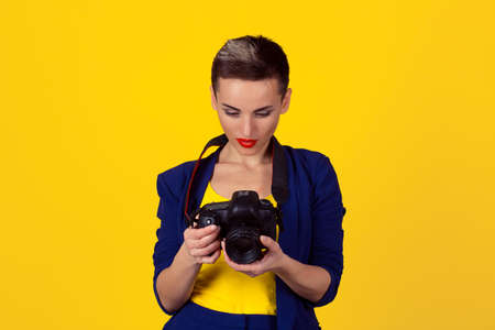 Beautiful smiling young business woman girl looking to taken pictures, images, photos isolated yellow background. Closeup portrait photographer using photographic reflex camera. Sweet memories concept