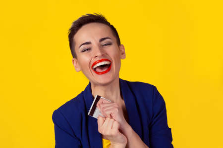 Close up portrait business woman with credit card smiling looking at camera you red lips  short hair boy alike isolated yellow background. Shopping credit banking concept. Studio shot horizontal image