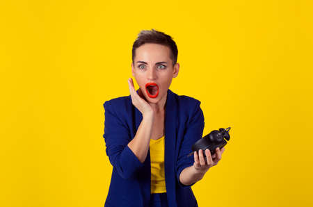 Closeup portrait young pretty beautiful business woman frustrated by lack of time to perform all duties for the day isolated yellow background. Negative emotion facial expression feeling body language Reklamní fotografie