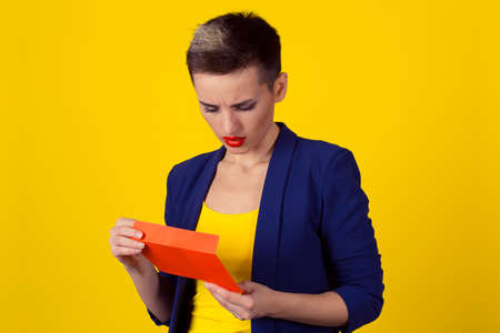 Closeup portrait unhappy business woman holding opening letter looking inside blue suit shirt, isolated yellow background. Bad news concept. Horizontal image studio shot half length body