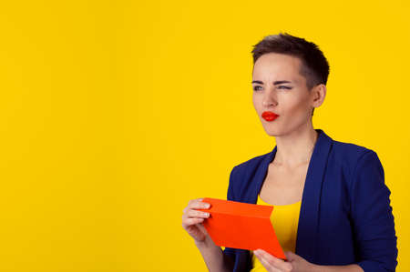 Thoughtful woman holding red envelope with money cash in it thinking what to do next, daydreaming planning how to spend them isolated yellow background wall
