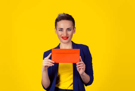 Happy smiling woman holding red envelope – isolated yellow background wall. studio shot horizontal image. Portrait with copy space 免版税图像