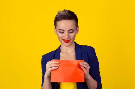 Fresh mail bribery concept. Closeup portrait business woman in blue formal suit, shirt received an envelope looking inside curious pleased by what she saw isolated yellow background with copy space