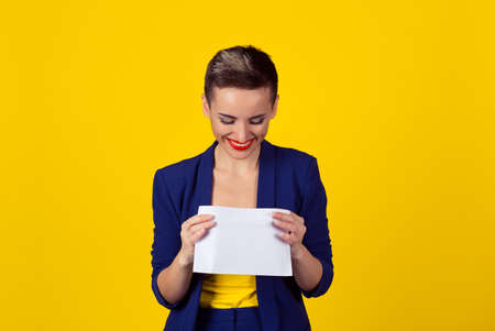 Attractive happy young business woman smiling opening looking inside a white envelope or letter to the camera with a pleased smile isolated yellow background wall with copy space. Fresh mail is here Reklamní fotografie