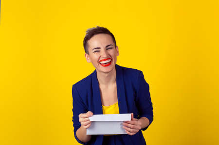 Happy woman smiling holding envelope letter isolated yellow background wall. Positive face expression human emotion body language Reklamní fotografie