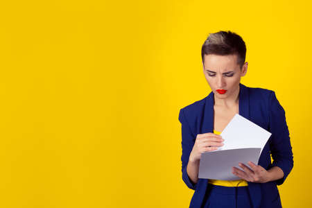 New contract concept. Business woman blue formal suit shirt looking at analyzing papers documents isolated yellow background wall