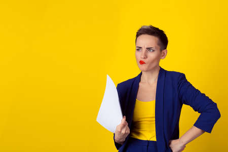 Skeptical about new contract. Business woman blue formal suit shirt looking up thinking analyzing holding papers documents isolated yellow background wall