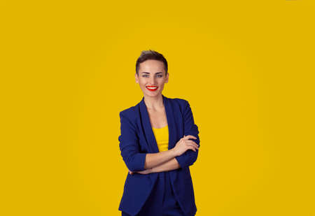 Success. Closeup portrait head shot confident beautiful happy young woman arms crossed smiling isolated yellow background wall. Positive human emotion face expression feeling life perception  attitude