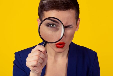 Skeptical woman looking through magnifying glass isolated yellow wall background. Funny woman skepticism concept. Positive human emotion face expression body language Focus on eye looking through lens