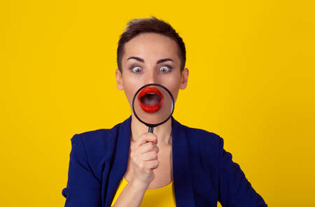 Amazed surprised woman looking down with magnifying glass on mouth isolated yellow wall. Funny woman, discover concept. Positive human emotion face expression body language Reklamní fotografie