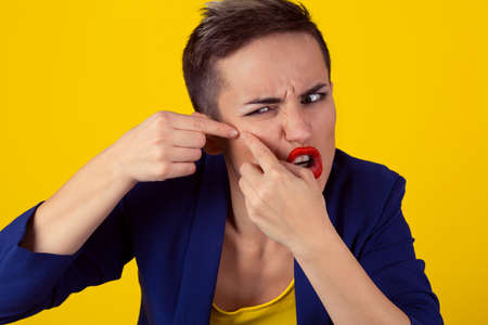 Closeup Portrait frustrated young business woman has find problems with the skin, squeezing a pimple on her cheek isolated yellow background. Negative human emotion, face expression, body language Reklamní fotografie