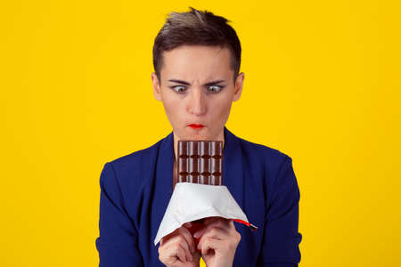 Crazy for chocolate. Closeup Portrait of a young business woman girl craving for about to eat chocolate isolated yellow background