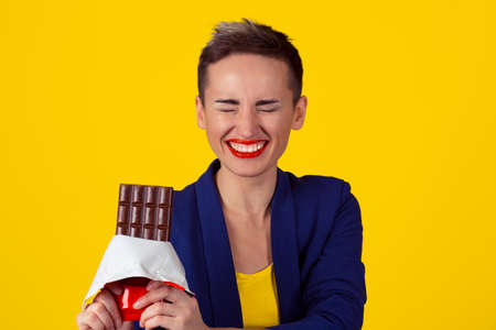 Woman with chocolate laughing. Closeup portrait young woman red lips laughing eating cocoa chocolate bar eyes closed happy isolated yellow background wall