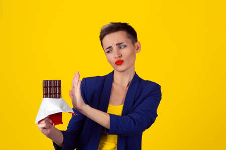 Not for me, thank you concept. Closeup Portrait of a young determined fit business woman girl refusing to eat chocolate isolated yellow background