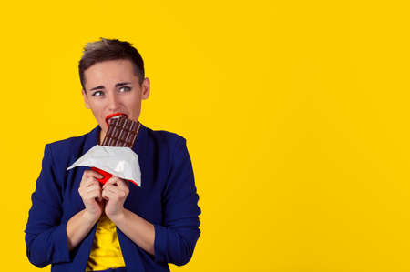 Woman tired of diet restrictions craving sweets chocolate. Closeup portrait Girl eating biting chocolate bar isolated yellow background wall