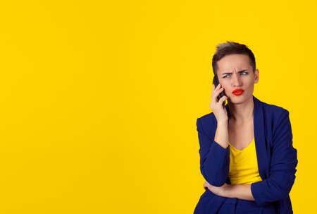 Skeptical business woman in disbelief talking on phone deciding what to answer looking to copy space isolated yellow background wall. Negative human emotion, face expression, body language