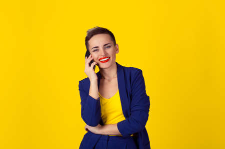 Staying connected. Happy young woman looking at you camera talking at her mobile phone and smiling isolated yellow wall background with copy space. Positive human emotion, face expression