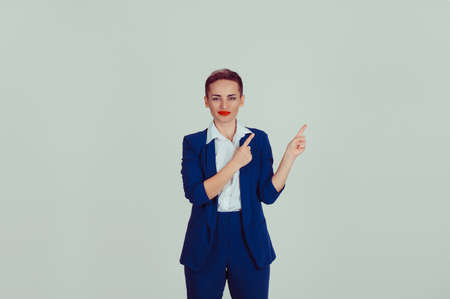 Smiling corporate lady pointing away to copy space light green background wall