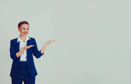 Cheerful business lady pointing away over light green copy space background wall