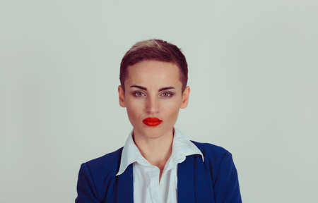 Attractive serious woman isolated green grey background with copy space. Short hair, blue navy suit, white buttoned shirt. Blue collar corporate employee Reklamní fotografie