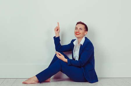 Woman smiling listening music in headphones on the floor in her room, studio isolated white bricks wall. Reklamní fotografie