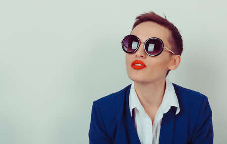 closeup portrait, confident, successful, beautiful attractive young woman, fashion girl, posing with sunglasses, isolated bright green background wall. Positive human emotion, facial expression