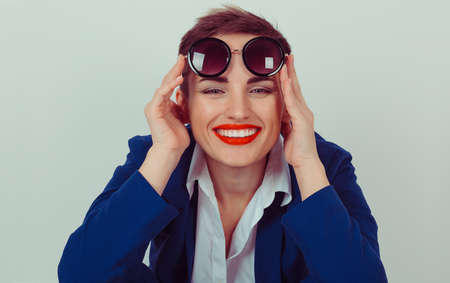 Portrait closeup attractive beautiful happy  successful young woman girl holding sunglasses smiling at camera isolated green background wall. Positive human emotion facial expression feeling attitude